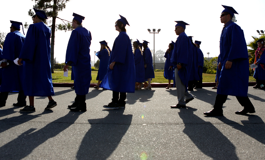 . Cabrillo College students are silhouetted against the cloudy Aptos sky as they march towards the football field to attend the 2013 Cabrillo College graduation ceremony. (Kevin Johnson/Sentinel)