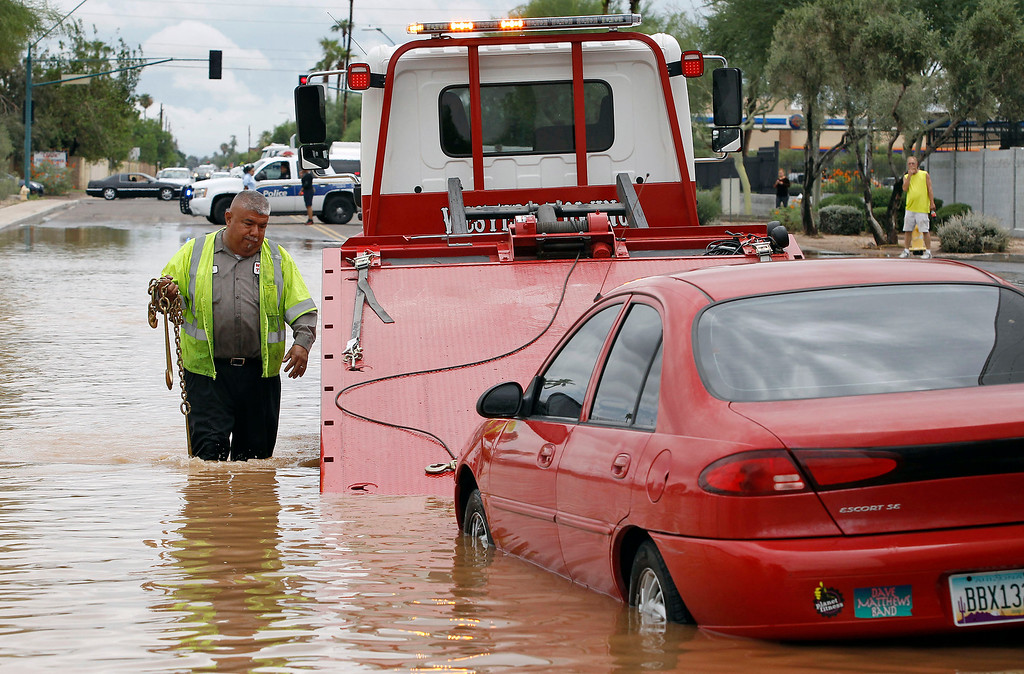 . Steven Martinez of Western Towing prepares to lift a vehicle stranded in about two feet of water near Roosevelt and 44th Avenue on Monday, Sept. 8, 2014 in Phoenix. Monday\'s record breaking rainfall flooded several Phoenix-area freeways and local streets forcing closures with some areas reporting up to five inches of rain. (AP Photo/Ralph Freso)