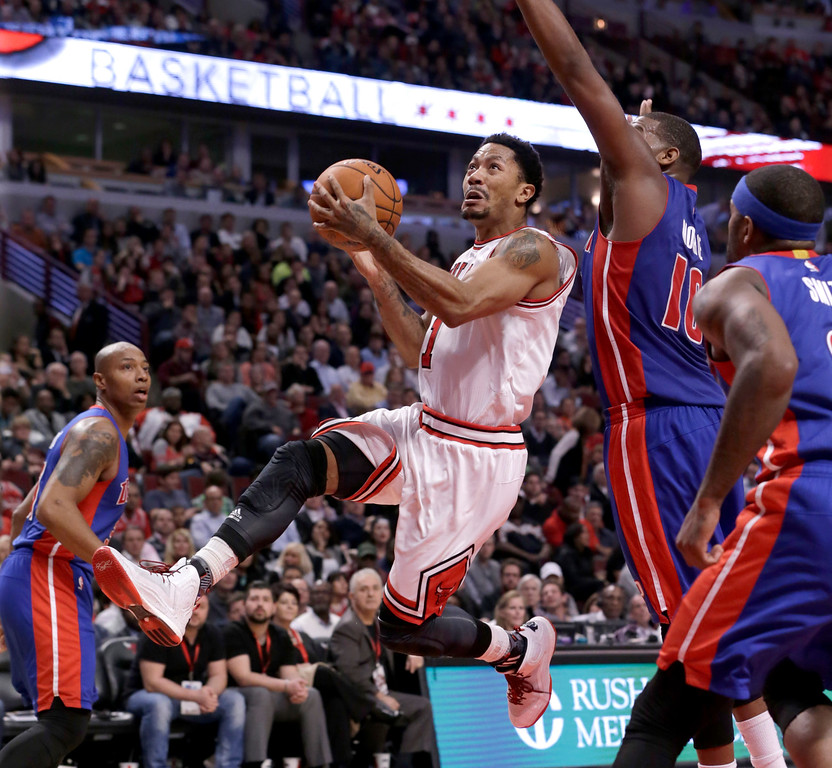 . Chicago Bulls guard Derrick Rose drives past Detroit Pistons forward Greg Monroe (10) during the second half of an NBA basketball game Monday, Nov. 10, 2014, in Chicago. The Bulls won 102-91. (AP Photo/Charles Rex Arbogast)