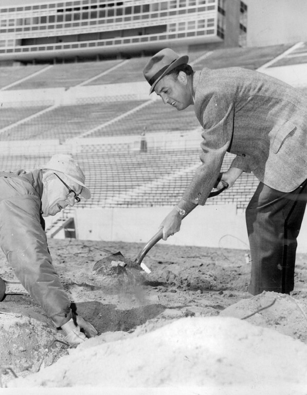. Air Force Academy Football Coach Ben Martin on the business end of the shovel, assists electrical technician Tom Nichols in covering wire, which serves to heat the grass in Falcon Stadium in 1966. By keeping the soil heated, the season for growing grass on he field will be extended. The Denver Post Library Archive