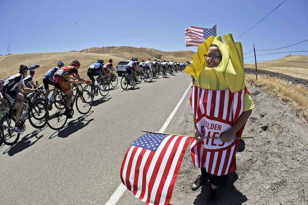 . George Dluzak, of Lathrop, Calif., 10, at right, cheers on the peloton during stage 7 of the Tour of California cycling race in Livermore, Calif., Saturday, May 18, 2013. (AP Photo/Marcio Jose Sanchez)