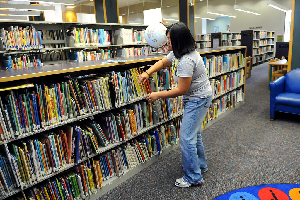 . Tania Pinon organizes a book shelf at the the Mid-Valley Library January 10, 2014 in North Hills, CA.  Starting January 12, 2014 the Los Angeles Public Library�s Central Library and eight regional branch libraries will be open on Sundays from 1 to 5 p.m.(Andy Holzman/Los Angeles Daily News)