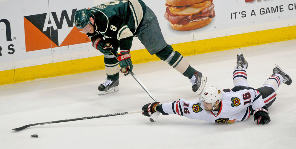 . Minnesota\'s Mikko Koivu, top, skates after the puck past a prone Marcus Kruger of the Blackhawks during the first period.   (Pioneer Press: Sherri LaRose-Chiglo)
