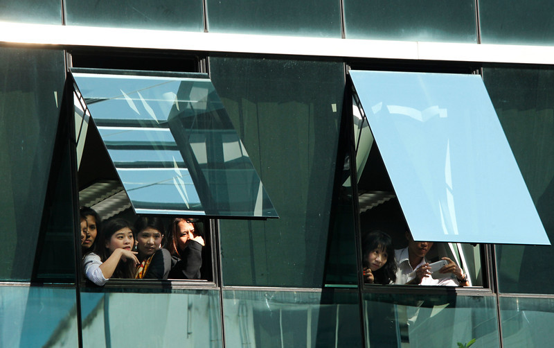 . Supporters of the anti-government movement struggle to get a view out their office windows of the passing demonstration in Bangkok, Thailand, Tuesday, Jan. 21, 2014. Thailand has declared a state of emergency in Bangkok and its surrounding areas to cope with anti-government protests that have stirred up violent attacks. (AP Photo/Wally Santana)
