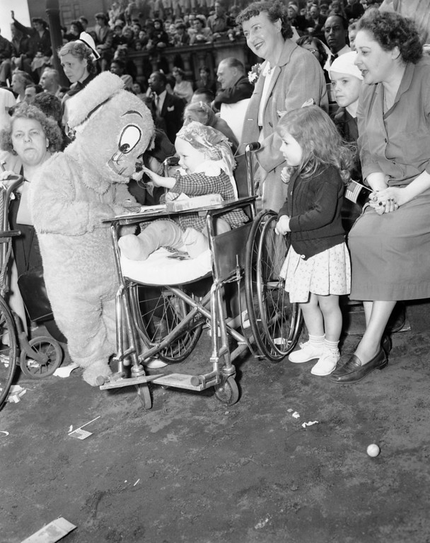 . Three-year-old Freddie Weber, a patient at Bellevue Hospital, New York, reaches gingerly to touch the nose of a teddy bear outfit worn by a clown as the Ringling Brothers Barnum and Bailey Circus took over at the hospital for their annual performance in New York on April 21, 1950. Some 6,000 men, women and children, many of them in wheel chairs and on stretchers, saw 13 circus acts while clowns ran all over the place to entertain the patients. (AP Photo/Tom Fitzsimmons)