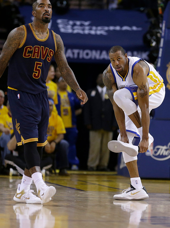 . Golden State Warriors forward Andre Iguodala, right, puts on his shoe next to Cleveland Cavaliers guard J.R. Smith (5) during the second half of Game 1 of basketball\'s NBA Finals in Oakland, Calif., Thursday, June 4, 2015. The Warriors on 108-100 in overtime. (AP Photo/Ben Margot)