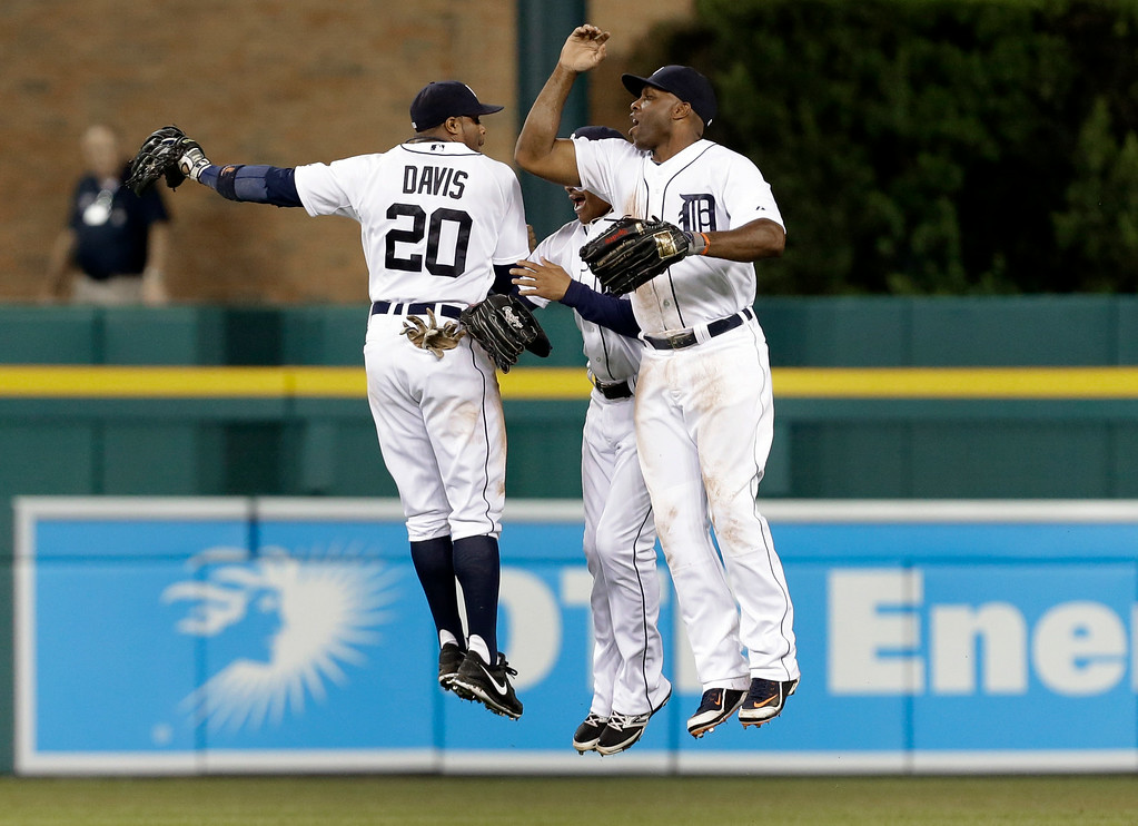. Detroit Tigers outfielders Rajai Davis (20), Ezequiel Carrera, center, and Torii Hunter celebrate after beating the New York Yankees 5-2 in a baseball game in Detroit Tuesday, Aug. 26, 2014. (AP Photo/Paul Sancya)