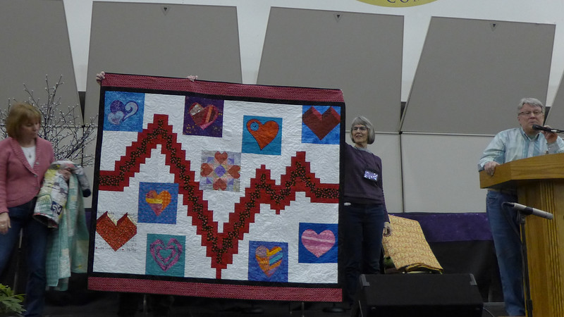 """The Beat Goes On"".  John Putnam is showing us a quilt that he received from the LALAs.  Lansing Area Long Armers.  they gave it to him as a wish for quick and speedy recovery from upcoming Aortic Valve Replacement.  Original design by Alicia DeBello, quilted by Nancy Boyse."