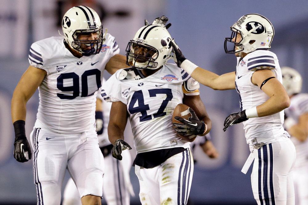 . BYU linebacker Ezekiel Ansah, center, is congratulated by Bronson Kaufusi, left, and Daniel Sorensen after intercepting a San Diego State pass during the first half of the Poinsettia Bowl NCAA college football game, Thursday, Dec. 20, 2012, in San Diego. (AP Photo/Lenny Ignelzi)