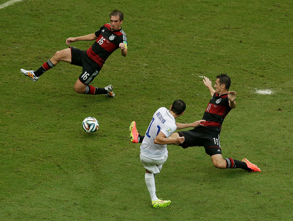 . United States\' Alejandro Bedoya takes a shot against Germany\'s Philipp Lahm and Germany\'s Miroslav Klose, right, during the group G World Cup soccer match between the USA and Germany at the Arena Pernambuco in Recife, Brazil, Thursday, June 26, 2014. (AP Photo/Hassan Ammar)
