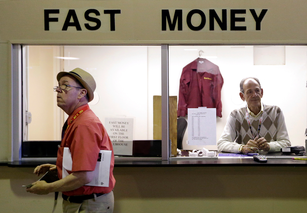 . Teller Lou Lanehardt, right, waits for customers in a booth at Pimlico Race Course in Baltimore, Saturday, May 17, 2014, before the 139th running of the Preakness Stakes horse race. (AP Photo/Patrick Semansky)