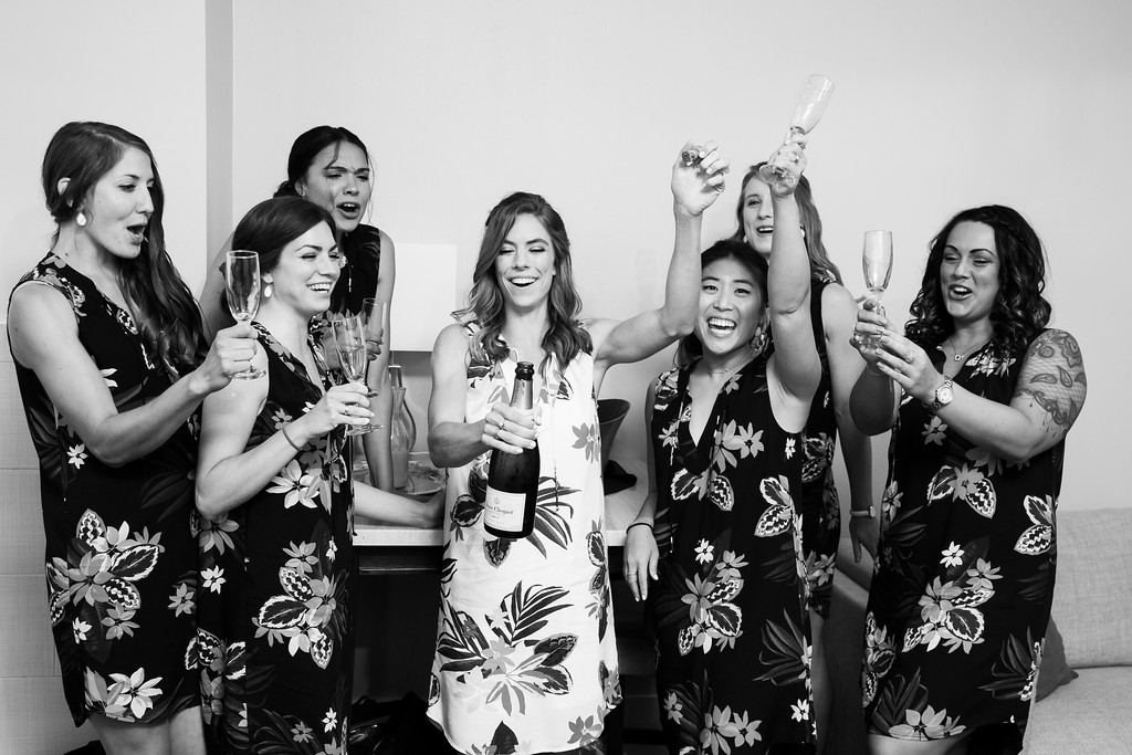 bride opening a bottle of champagne while surrounded by her bridesmaids