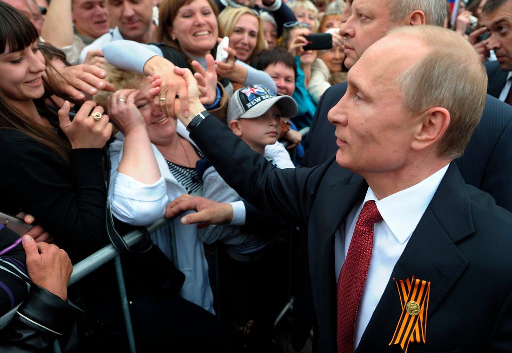 . Russian President Vladimir Putin, center, is greeted by people in Sevastopol where he attends celebrations marking  the Victory Day, Crimea, Friday, May 9, 2014. (AP Photo/RIA-Novosti, Alexei Druzhinin, Presidential Press Service)