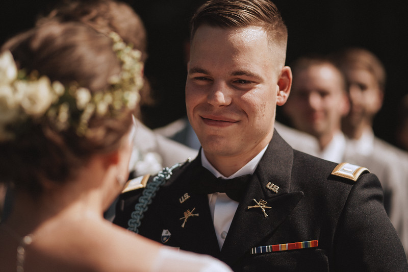 Groom smiling as he looks into his bride's eyes.