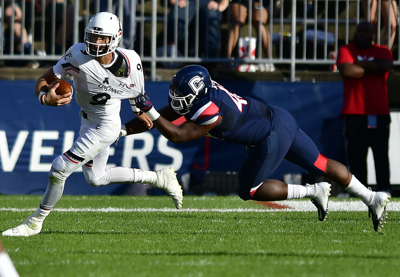9/29/2018 Mike Orazzi | Staff Cincinnati's Desmond Ridder (9) and UConn's Kevon Jones (48) Saturday in East Hartford.