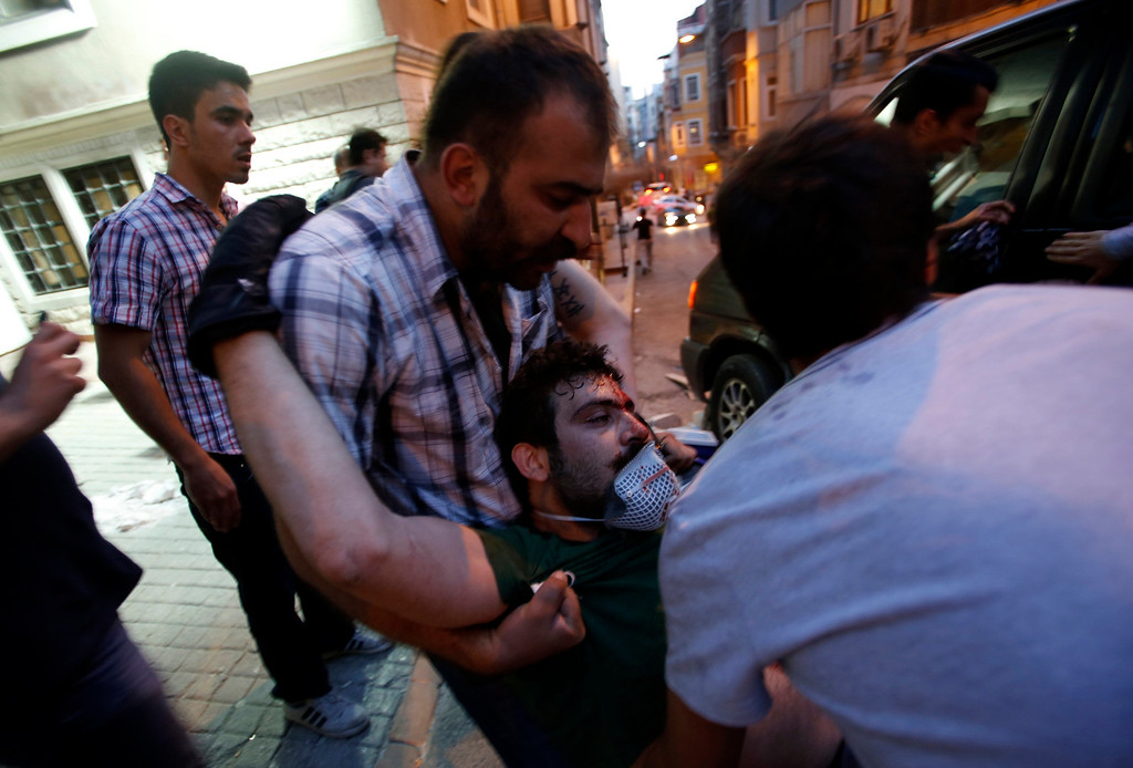 . An injured demonstrator is carried by his friends as they clash with riot police during an anti-government protest at Taksim Square in central Istanbul May 31, 2013. Turkish police fired tear gas and water cannon on Friday at demonstrators in central Istanbul, wounding scores of people and prompting rallies in other cities in the fiercest anti-government protests for years. REUTERS/Murad Sezer