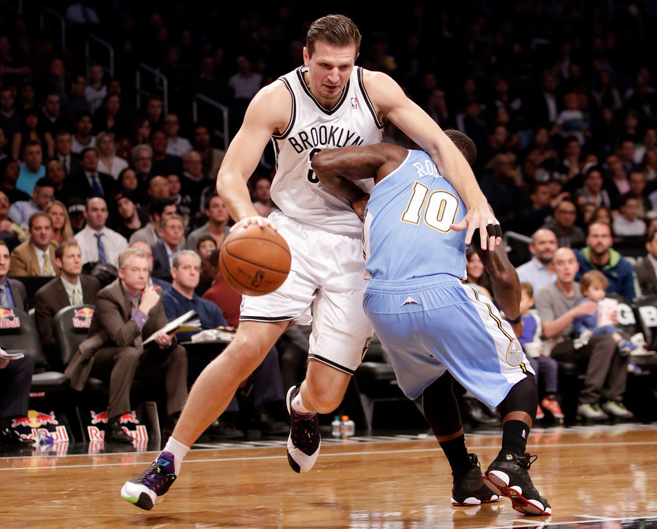 . Brooklyn Nets forward Mirza Teletovic, left, runs into Denver Nuggets point guard Nate Robinson (10) in the first half of an NBA basketball game Tuesday, Dec. 3, 2013, in New York. (AP Photo/Kathy Willens)