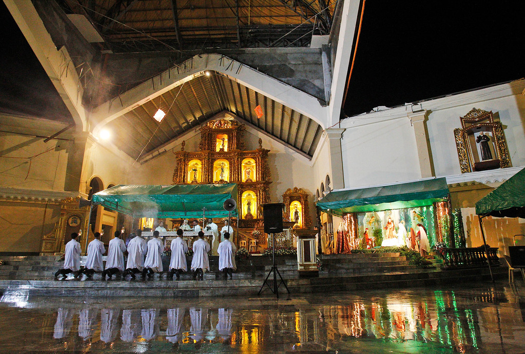 . A preacher pray\'s during final dawn mass on Christmas eve at Palo Cathedral church in Palo, Leyte province in central Philippine, Wednesday, Dec. 25, 2013. The Christmas eve mass took place in the area devastated by the Nov. 8 typhoon Haiyan\'s ferocious winds and the tsunami-like storm surge. (AP Photo/Achmad Ibrahim)