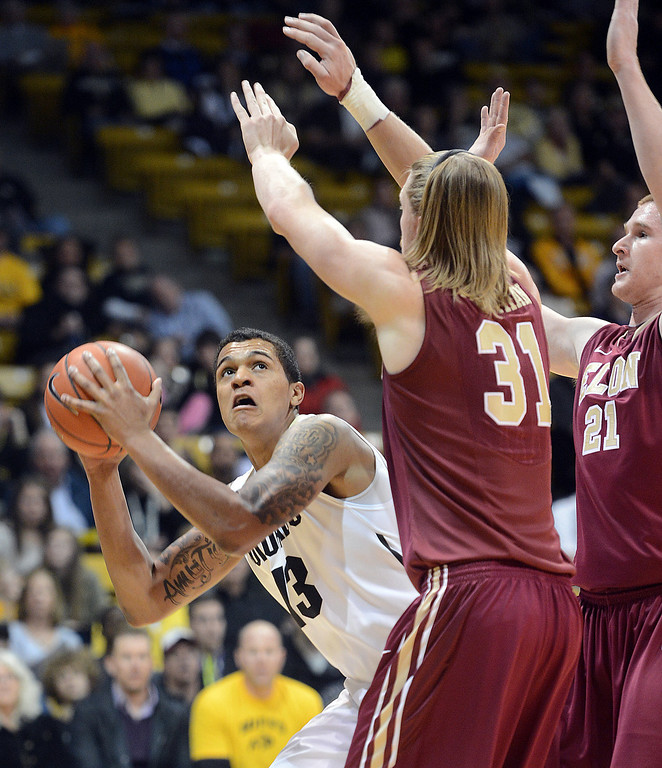 . Dustin Thomas of CU shoots over Lucas Troutman of Elon during the first half of the December 13, 2013 game in Boulder. (Cliff Grassmick/Boulder Daily Camera)