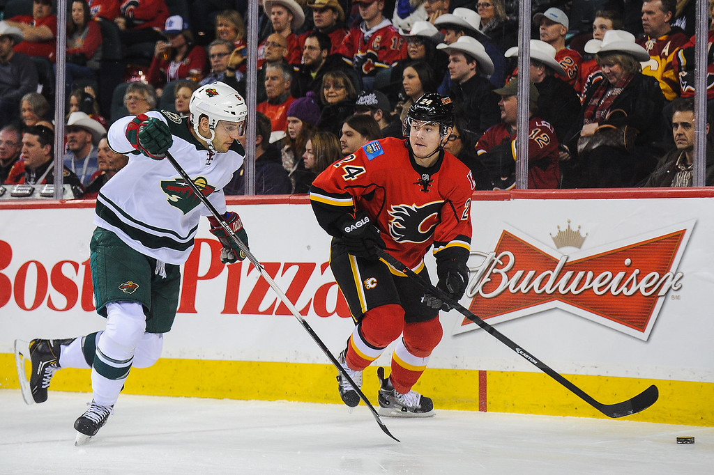 . Jiri Hudler #24 of the Calgary Flames chases the puck against Marco Scandella #6 of the Minnesota Wild during an NHL game at Scotiabank Saddledome on February 1, 2014 in Calgary, Alberta, Canada. (Photo by Derek Leung/Getty Images)
