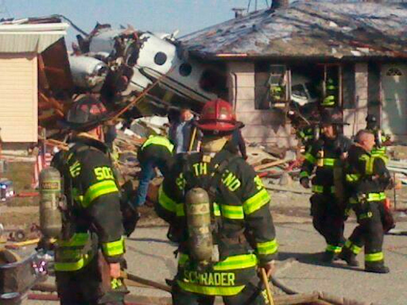 . Firefighters and rescue workers look over the scene in South Bend, Indiana in this March 17, 2013 photo courtesy WNDU-TV after a small twin-jet aircraft crashed into houses near the South Bend Regional Airport. At least three people were injured and multiple others were killed, authorities reported.   REUTERS/WNDU-TV/Handout