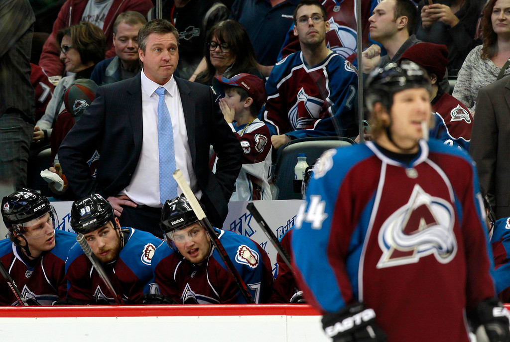 . Colorado Avalanche head coach Patrick Roy, back, watches his team in the second period of an NHL hockey game against the Winnipeg Jets in Denver on Sunday, Oct. 27, 2013. (AP Photo/David Zalubowski)