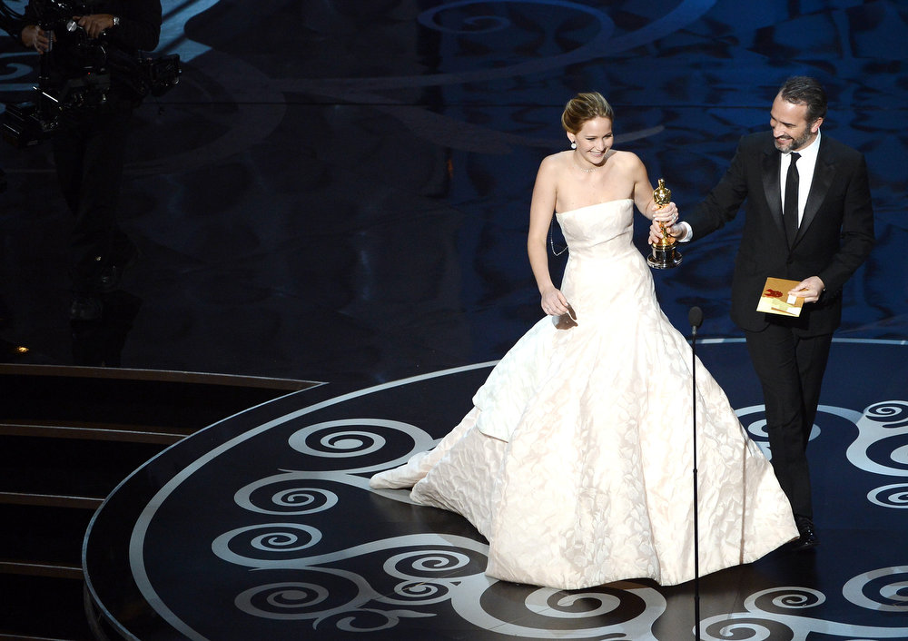 ". Actress Jennifer Lawrence accepts the Best Actress award for ""Silver Linings Playbook\"" from presenter actor Jean Dujardin during the Oscars held at the Dolby Theatre on February 24, 2013 in Hollywood, California.  (Photo by Kevin Winter/Getty Images)"