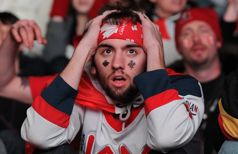 . Canadian fan react during the US versus Canada Ice Hockey game on a giant TV during the Vancouver Winter Olympics on February 21, 2010.  (MARK RALSTON/AFP/Getty Images)