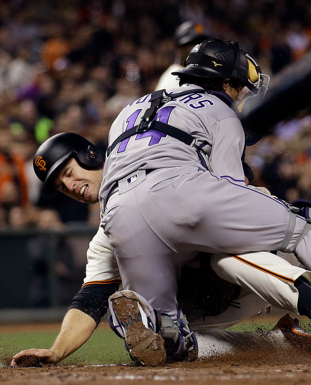 . San Francisco Giants\' Buster Posey, left, is tagged out at home plate by Colorado Rockies catcher Tony Wolters as Posey tried to score on a single from Brandon Crawford during the third inning of a baseball game Thursday, May 5, 2016, in San Francisco. (AP Photo/Marcio Jose Sanchez)