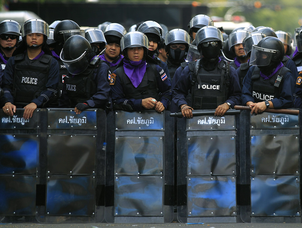 . Thai riot police officers stand guard near Government House in Bangkok, Thailand, 18 February 2014.   EPA/NARONG SANGNAK