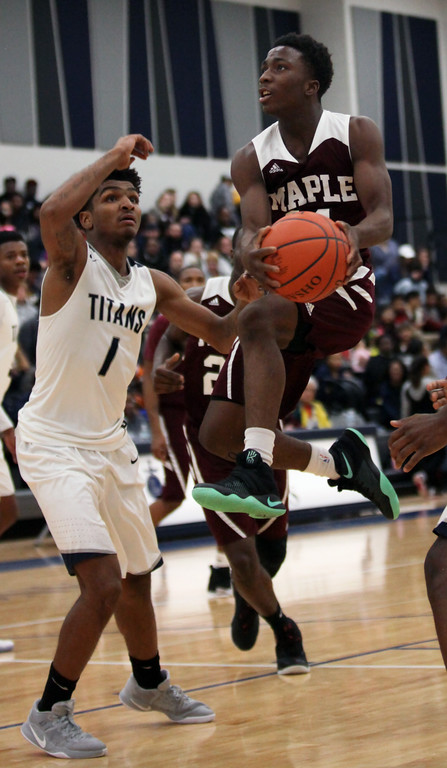 . Maple Heights guard Marcus Kimmie drives the lane past Octavious Wilson of Lorain during the third quarter. Randy Meyers -- The Morning Journal