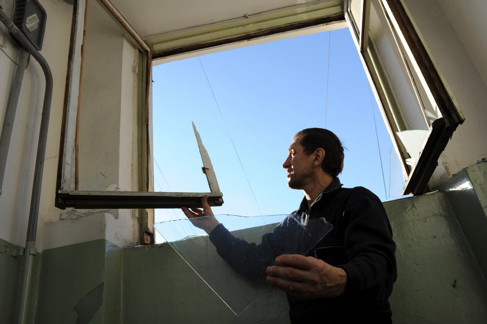 Description of . A local resident repairs a window broken by a shock wave from a meteor explosion in Chelyabinsk, about 1500 kilometers (930 miles) east of Moscow,  Friday, Feb. 15, 2013. A meteor that scientists estimate weighed 10 tons (11 tons) streaked at supersonic speed over Russia's Ural Mountains on Friday, setting off blasts that injured some 500 people and frightened countless more. (AP Photo/Boris Kaulin)