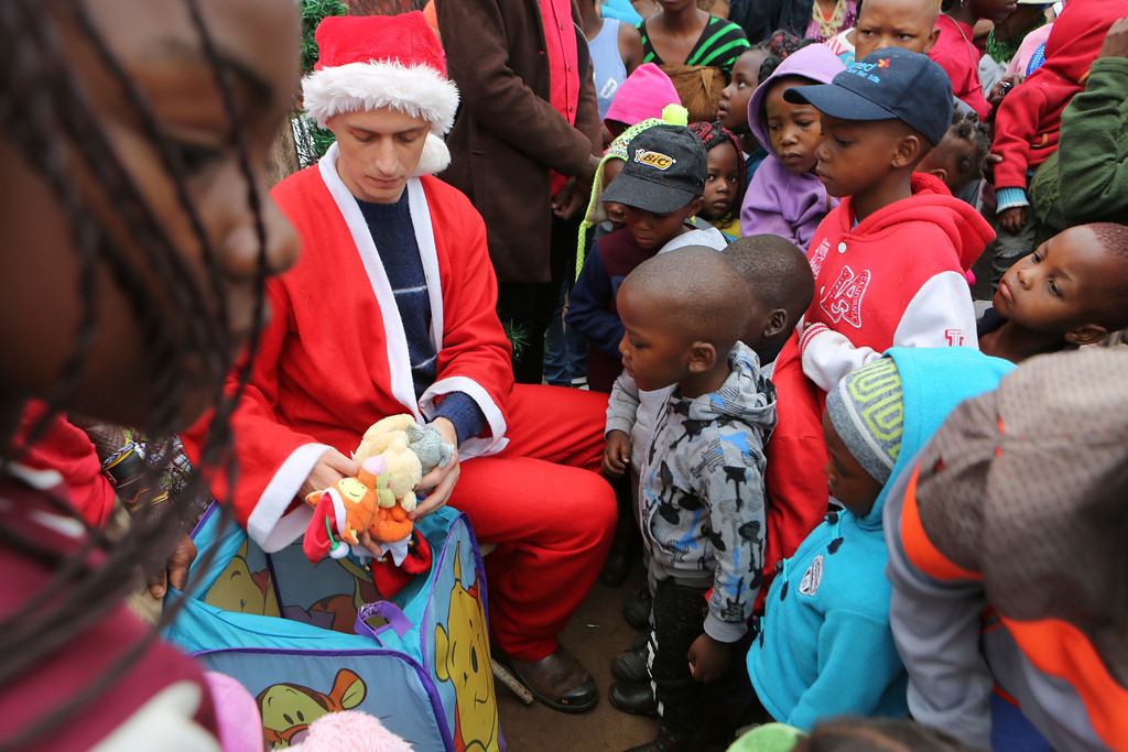 ". A man dressed as Santa working for a charity distributes gifts to children on Christmas morning to residents in the Joe Slovo squatter settlement near Johannesburg, Sunday Dec. 25, 2016.  The gifts are donated by the ""Children of Fire\"" charity which primarily aims to assists burn victims from across Africa.(AP Photo/Denis Farrell)"