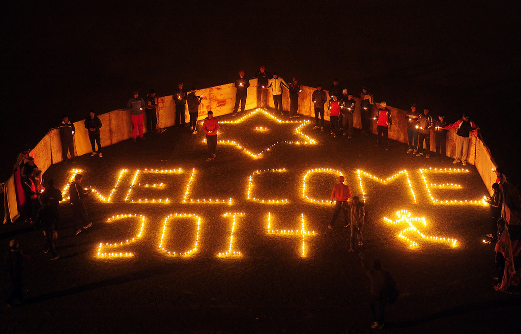 . Indian sports players from the Madan Mohan Malviya Stadium light candles during an event to welcome the New Year in Allahabad on December 31, 2013. People around the world are welcoming 2014.  Sanjay Kanojia/AFP/Getty Images