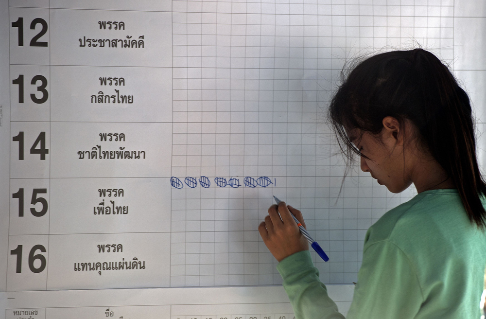 . A Thai election official writes as ballots are counted after voting ended at a polling station in Bangkok on February 2, 2014.  (PORNCHAI KITTIWONGSAKUL/AFP/Getty Images)
