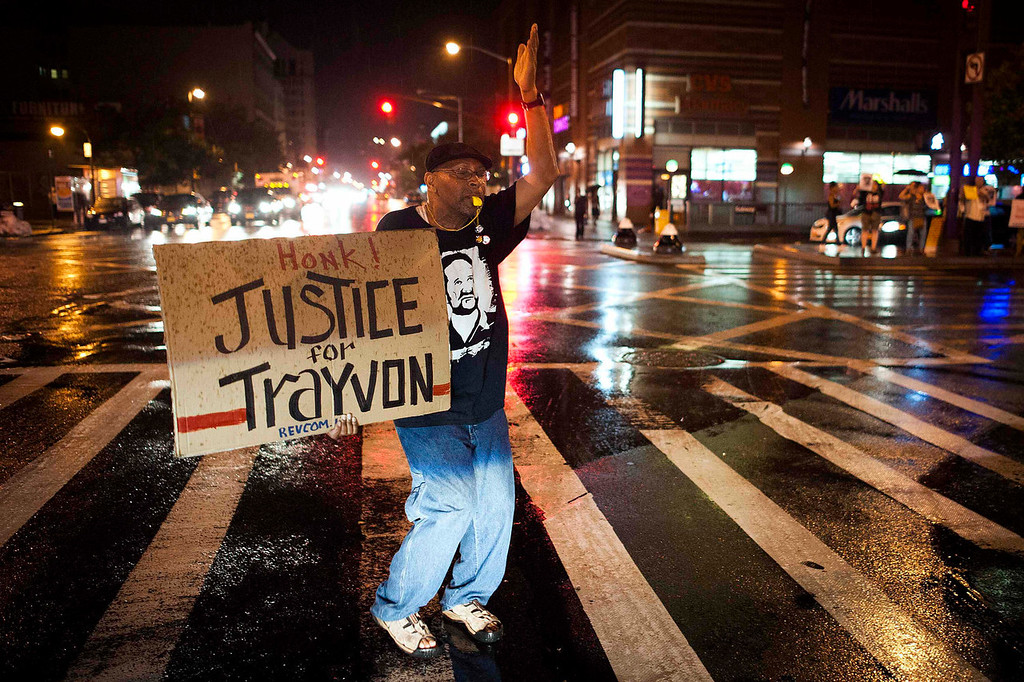 . Will Reese holds a protest sign in response to the acquittal of George Zimmerman in the Trayvon Martin trial, in the Harlem neighborhood of New York, July 14, 2013.A Florida jury acquitted George Zimmerman on Saturday in the shooting death of unarmed black teenager Trayvon Martin in a case that sparked a national debate over racial profiling and self-defense laws. REUTERS/Keith Bedford