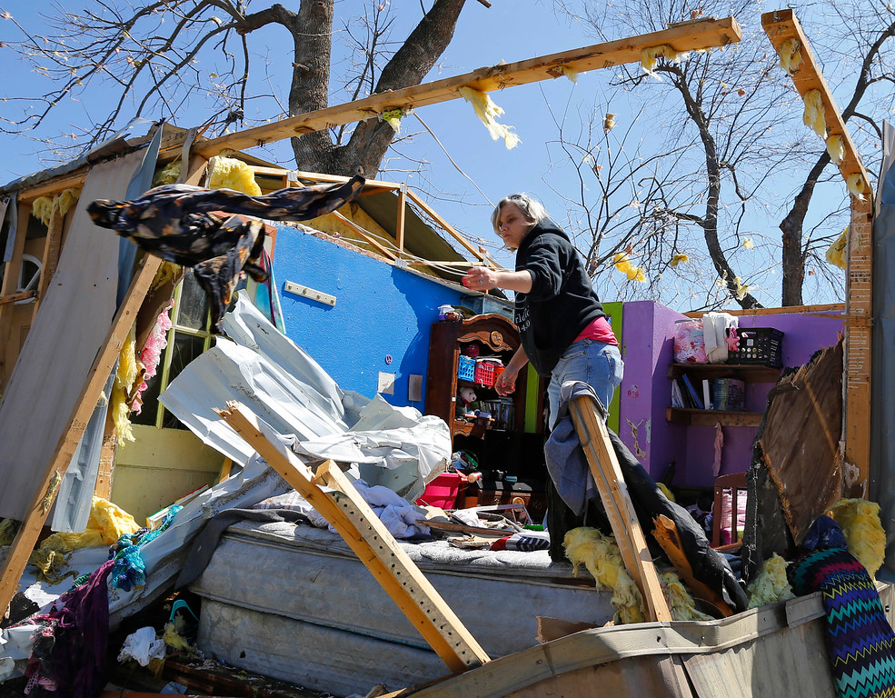 . Jamie Mull salvages an article of clothing from a friend\'s tornado-damaged mobile home in Sand Springs, Okla., Thursday, March 26, 2015. (AP Photo/Sue Ogrocki)