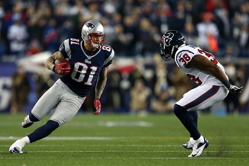 . Aaron Hernandez #81 of the New England Patriots runs with the ball against Danieal Manning #38 of the Houston Texans during the 2013 AFC Divisional Playoffs game at Gillette Stadium on January 13, 2013 in Foxboro, Massachusetts.  (Photo by Elsa/Getty Images)