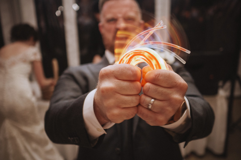 The groom grips a fist full of glow sticks and grimaces as he bends them.
