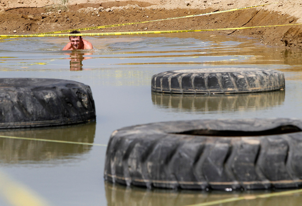 . A runner makes his way thru a mud pit during the Sheriff�s Athletic Federation\'s annual 5K Mud Run on Saturday, May 17, 2014 at the Sheriff�s Department Academy in Devore, Ca. (Photo by Micah Escamilla/San Bernardino Sun)