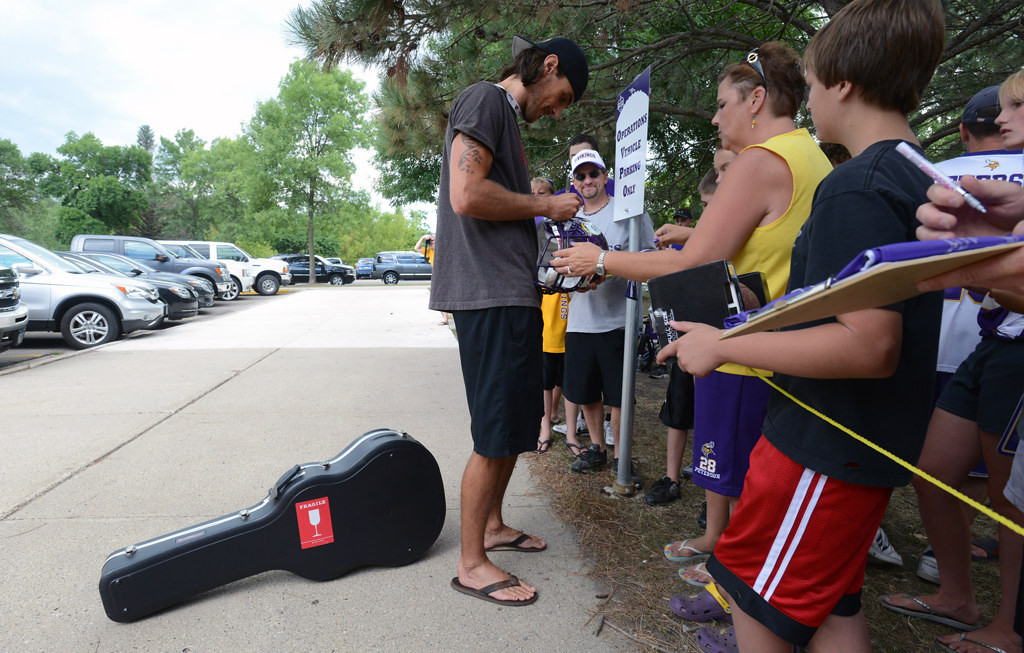 . Vikings\' Chris Kluwe set his guitar down to sign autographs for fans upon arriving at training camp at Mankato State University on Thursday July 26, 2012.   (Pioneer Press: Chris Polydoroff)