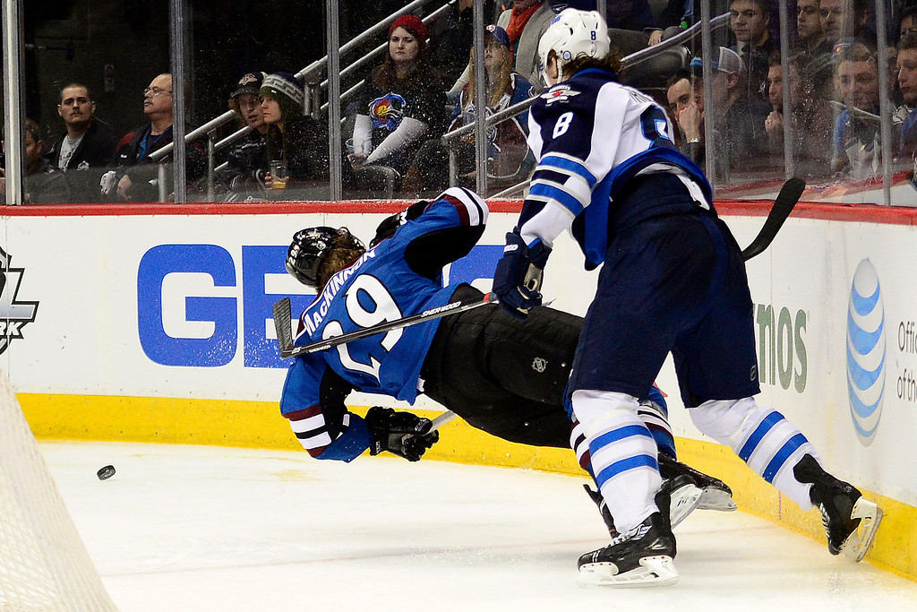 . Jacob Trouba (8) of the Winnipeg Jets lays out Nathan MacKinnon (29) of the Colorado Avalanche during the third period of action. The Colorado Avalanche lost 2-1 to the Winnipeg Jets at the Pepsi Center on Sunday, December 29, 2013. (Photo by AAron Ontiveroz/The Denver Post)