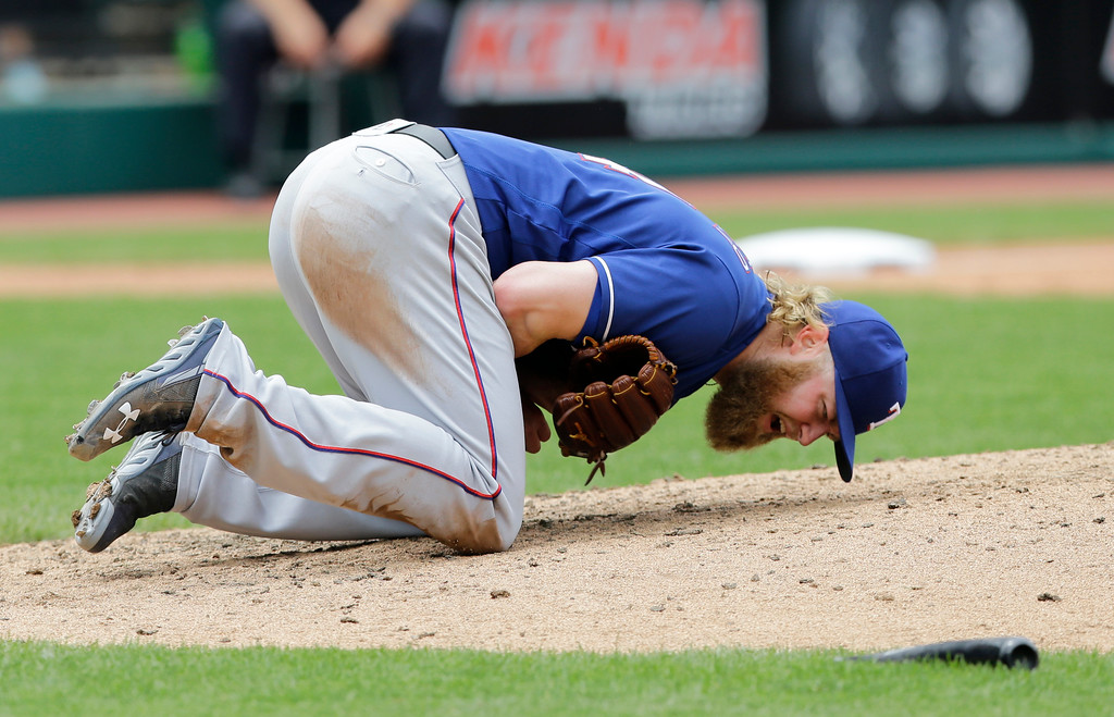 . Texas Rangers starting pitcher Andrew Cashner reacts after getting hit by the broken bat, foreground right, of Cleveland Indians\' Edwin Encarnacion in the sixth inning of a baseball game, Thursday, June 29, 2017, in Cleveland. Encarnacion was safe at first base. Michael Brantley scored on the play. (AP Photo/Tony Dejak)