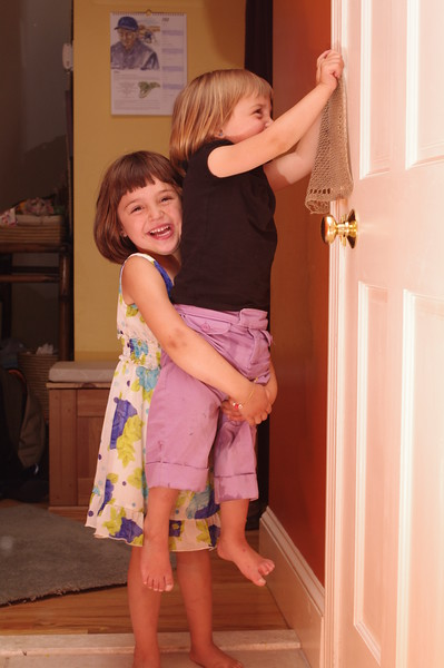 Now Anya cleans the doorframe, with a little help.