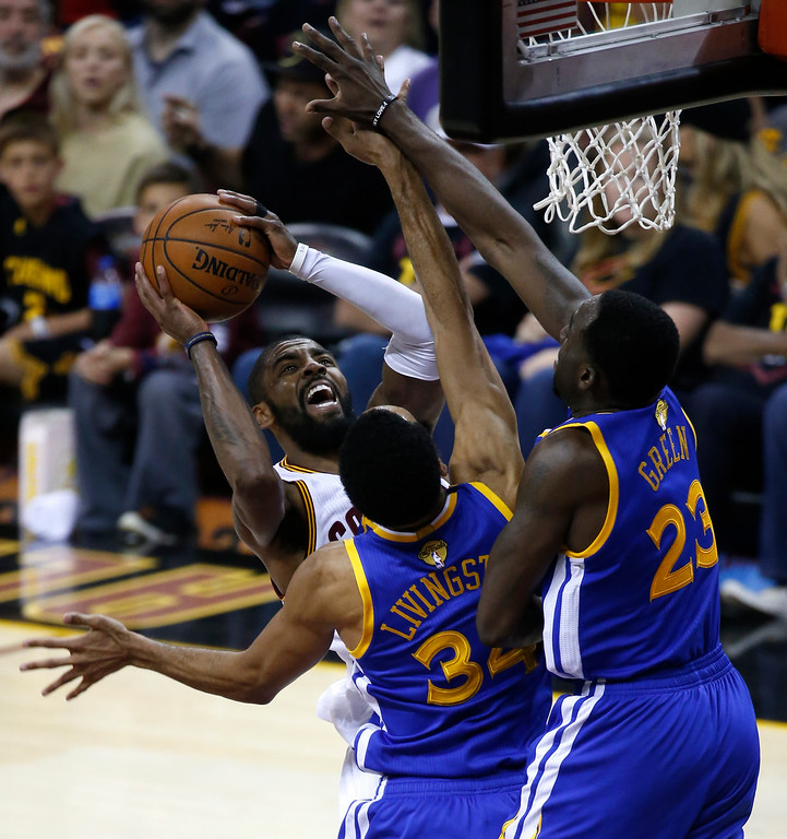 . Cleveland Cavaliers guard Kyrie Irving (2) drives on Golden State Warriors guard Shaun Livingston (34) and Draymond Green (23) during the first half of Game 3 of basketball\'s NBA Finals in Cleveland, Wednesday, June 7, 2017. (AP Photo/Ron Schwane)