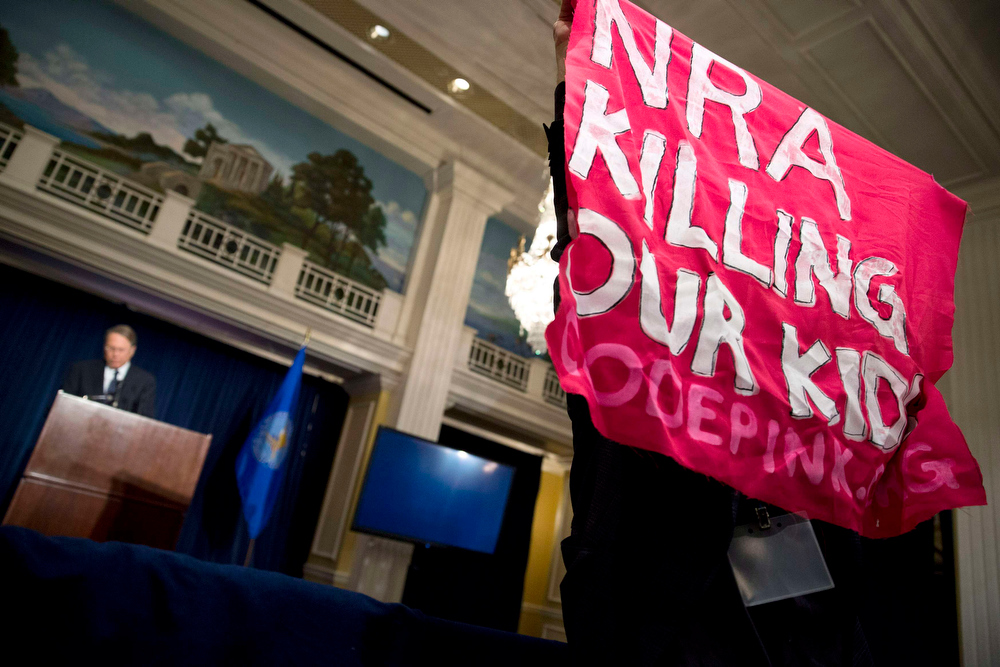 Description of . A protester holds up a sign during a speech by Wayne LaPierre (L), Executive Vice President of the National Rifle Association (NRA), during a news conference in Washington December 21, 2012. NRA, the powerful U.S. gun rights lobby, went on the offensive on Friday arguing that schools should have armed guards, on a day that Americans remembered the victims of the Newtown, Connecticut school massacre with a moment of silence.    REUTERS/Joshua Roberts