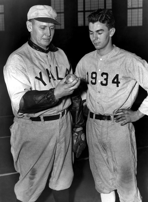 . Coach Joe Wood, of Yale, left, talks to one of his most promising 1935 baseball prospects, none other than Tad Jones, Jr., son of the late Yale coach in New Haven, Connecticut, Jan. 21, 1935. Young Jones is a twirler, and coach Wood says he�s got �a lot of stuff on the ball.� (AP Photo)