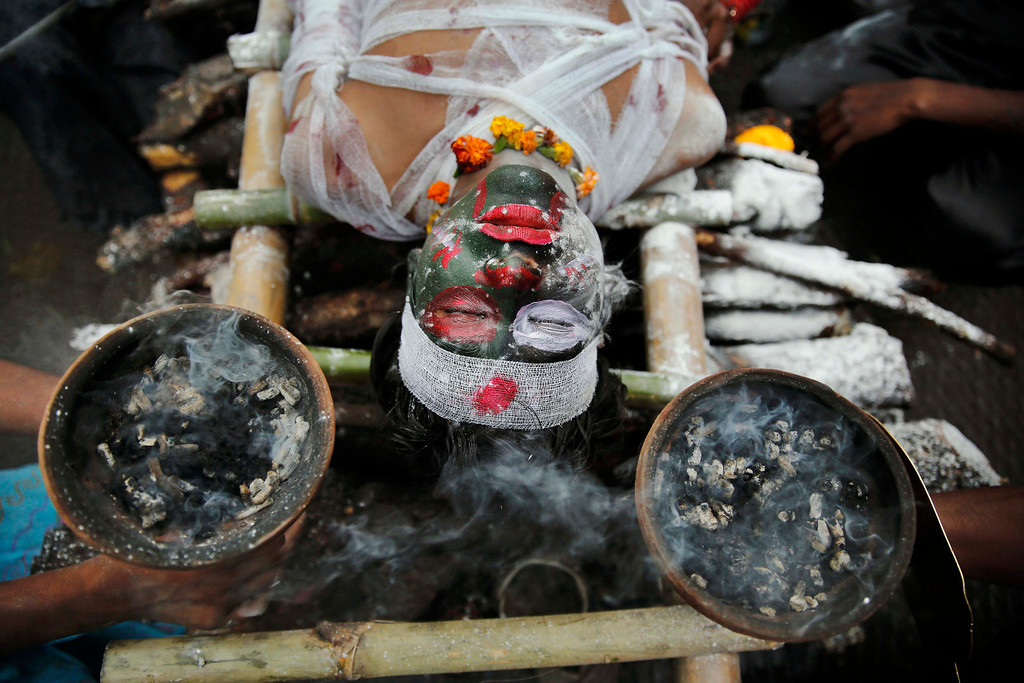 . A Hindu devotee dressed as s demon lies on a representative funeral pyre during a \'Shivratri\' procession in Allahabad, India, Thursday, Feb. 27, 2014.  (AP Photo/Rajesh Kumar Singh)