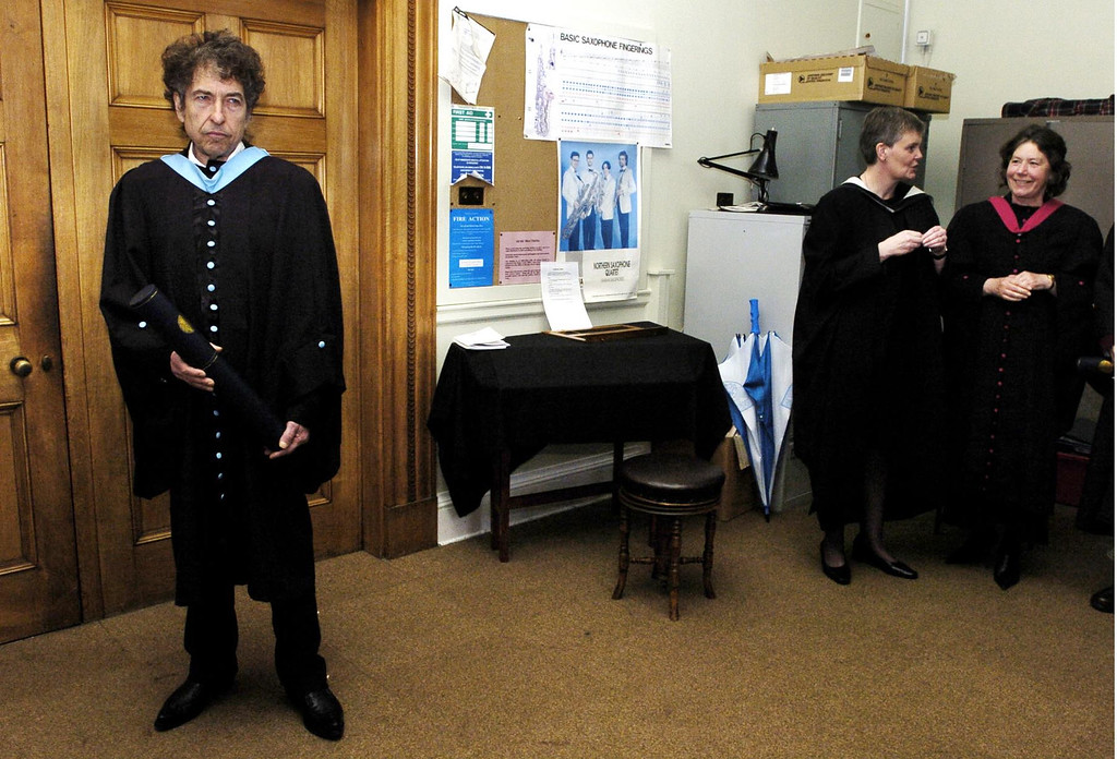 """. Rock legend Bob Dylan waits at the University of St. Andrews in Scotland,  as he is watched by two unidentified women, Wednesday, June 23, 2004, after he received an honorary degree of Doctor of Music.  The American icon, whose hits include \""""Like a Rolling Stone\"""" and \""""Mr Tambourine Man,\"""" has only ever accepted one other honorary degree, from Princeton University in 1970. (AP Photo/ Pool/David Cheskin)"""