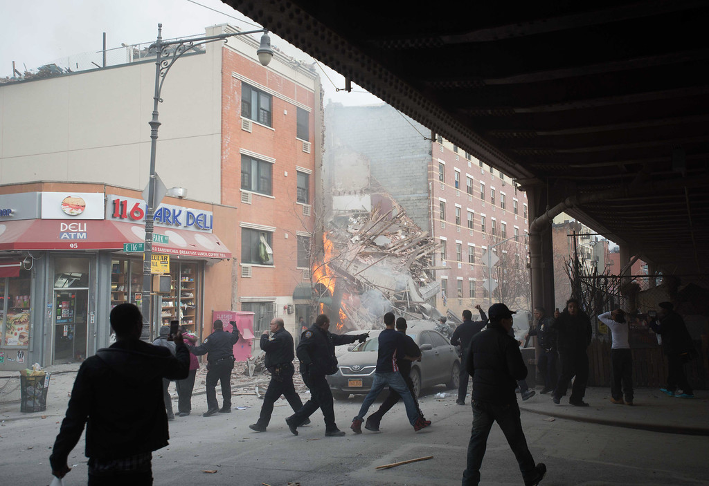 . Police move people away from the scene of an explosion and building collapse in the East Harlem neighborhood of New York, Wednesday, March 12, 2014.  (AP Photo/Jeremy Sailing)